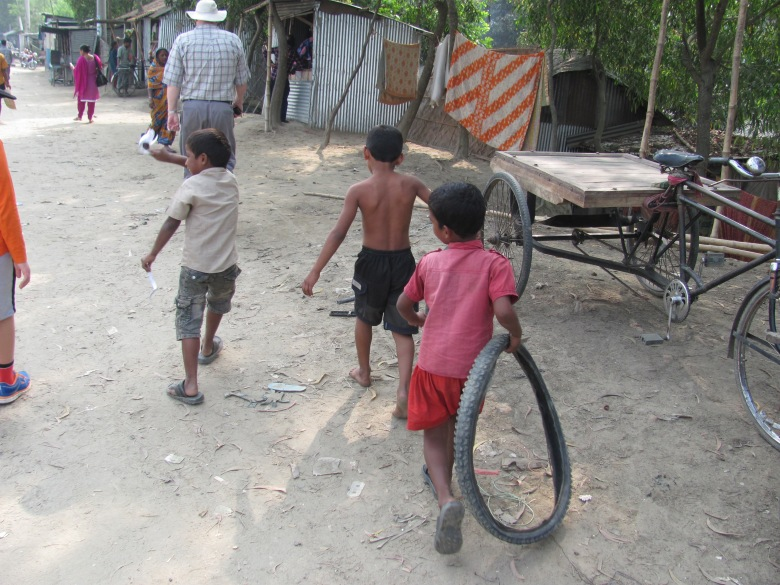 Children from the river slum plays with sticks and old tyres - Mymensingh, Bangladesh