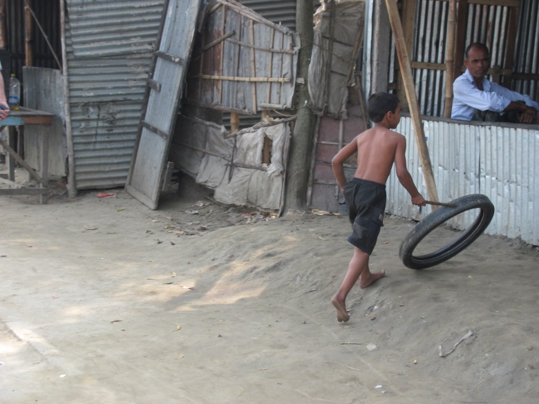 A boy from the river slum plays with a stick and an old tyre - Mymensingh, Bangladesh